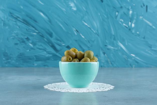 Olives vertes dans un bol sur un sous-verre , sur la table en marbre.