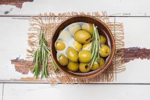 Olives vertes dans des bols en bois sur table en bois. vue de dessus avec espace pour le texte.
