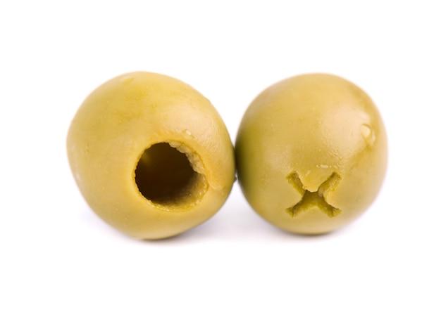 Olives vertes dénoyautées et marinées dans un bol en bois, isolé sur un espace blanc.