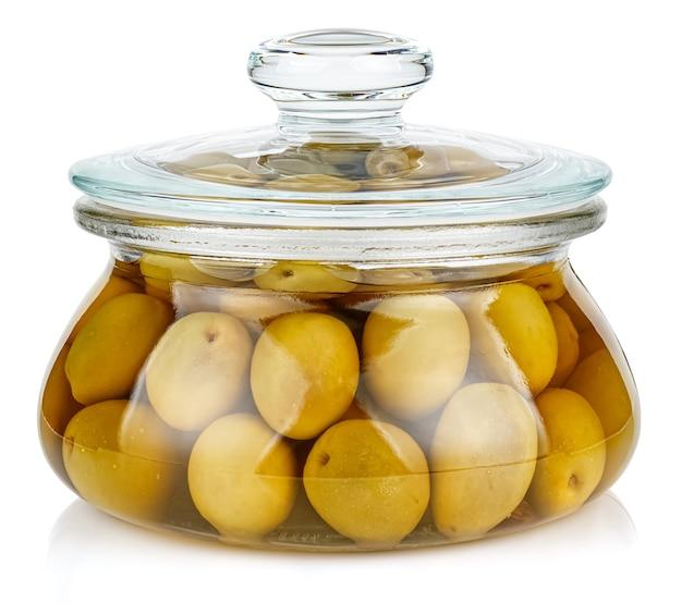 Olives vertes entières en saumure dans un bocal de rangement ovale en verre transparent fermé avec couvercle en verre isolé sur fond blanc