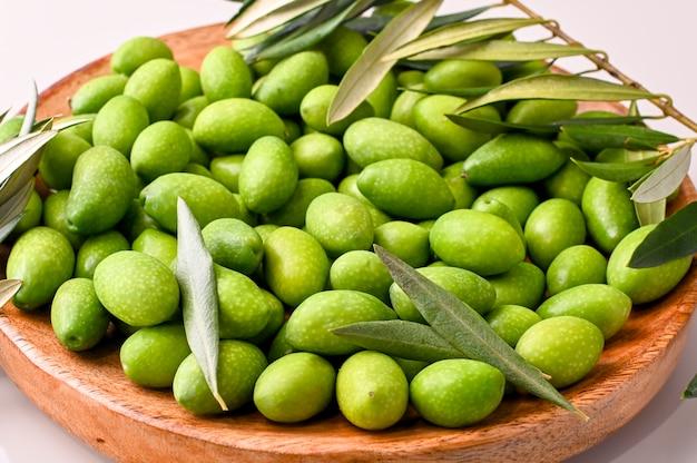 Olives vertes fraîches avec des branches et des feuilles. récolte saisonnière en italie. vue de dessus.
