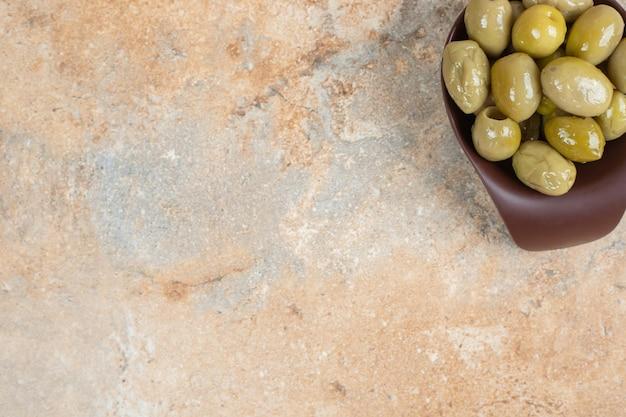 Olives vertes marinées dans un bol sombre.