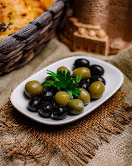 Olives vertes et noires décorées de persil