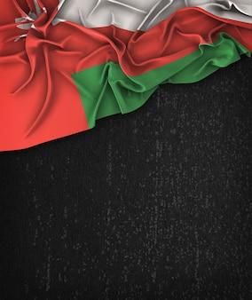 Oman flag vintage sur un tableau noir grunge avec un espace pour le texte