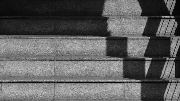 L'ombre de la balustrade en fer sur l'escalier en béton