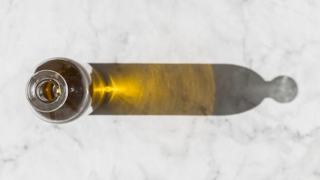 Ombre de la bouteille d'huile sur fond de marbre blanc