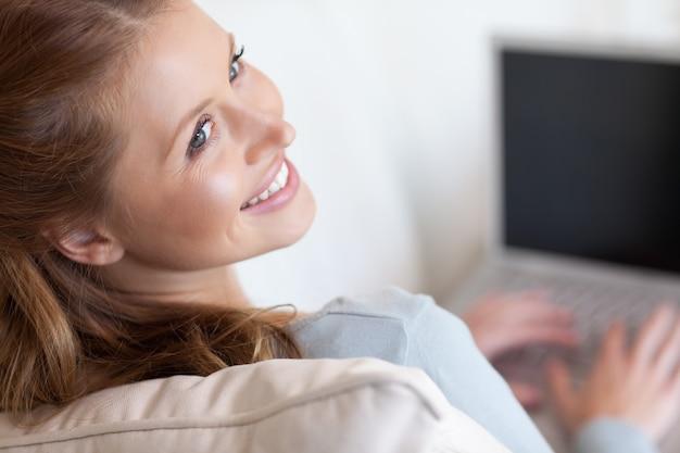 Ombre femme souriante travaillant sur son ordinateur portable