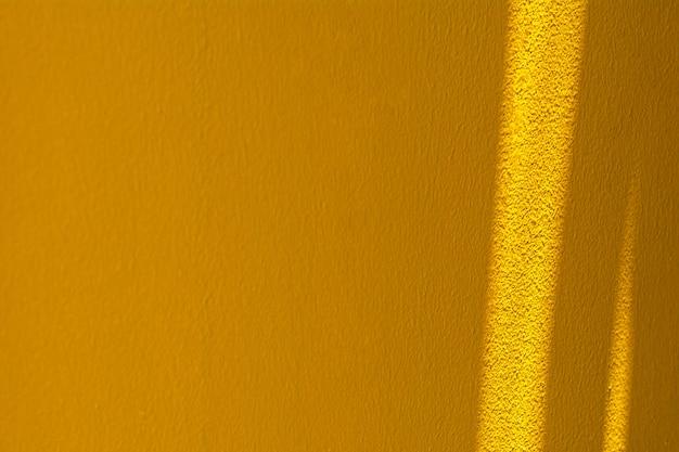 Ombre de la fenêtre en verre au mur de béton jaune.