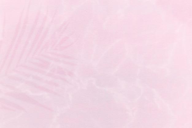 Ombre de feuille de palmier sur un fond rose clair