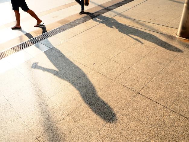Ombre de gens sur le trottoir. ombres de personnes dans une ville pendant le coucher du soleil.