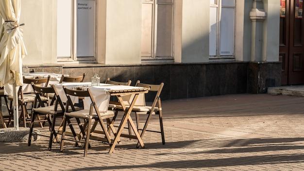 Ombre et lumière des tables à l'extérieur du restaurant en attente de clients le soir dans la rue piétonne dite rue arbut , moscou , russie
