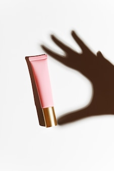 Ombre d'une main avec un tube rose de crème