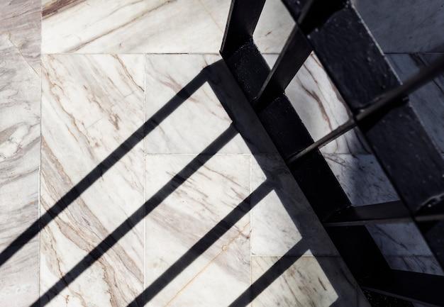 Ombre d'une porte en fer forgé sur un sol en marbre blanc