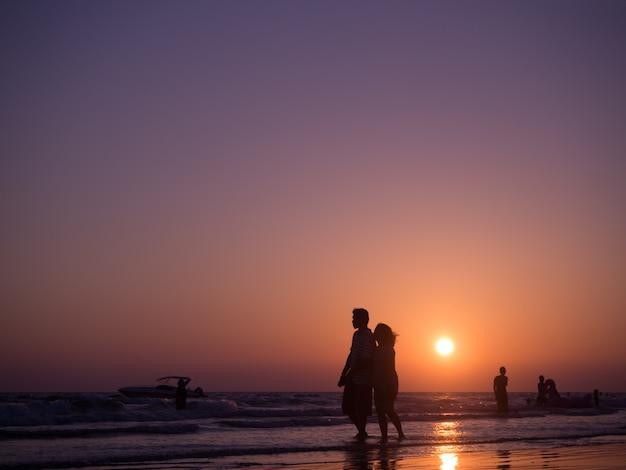 Ombre silhouette de couple amoureux marchant sur la plage avec coucher de soleil. concept de plage de vacances