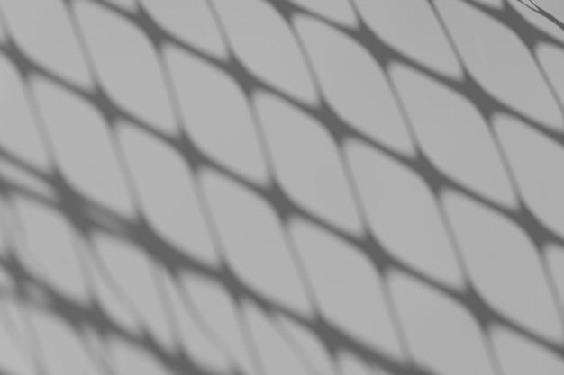 Ombre en treillis de superposition d'ombres à motifs sur un mur blanc lors d'une journée ensoleillée photo de haute qualité