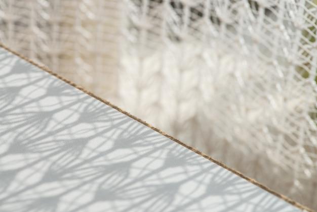 Ombre de tulle à motifs sur une surface en bois blanche