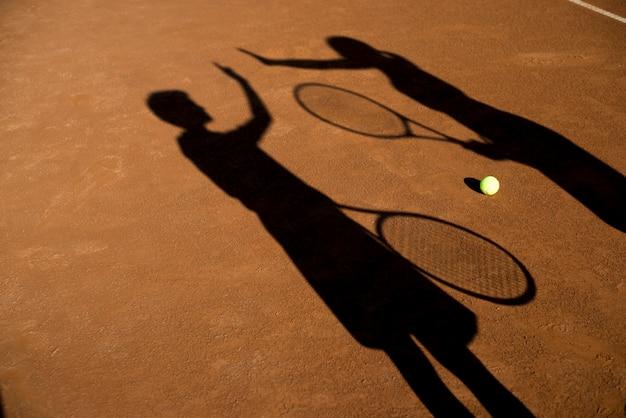 Ombres de deux joueurs de tennis haut fiving