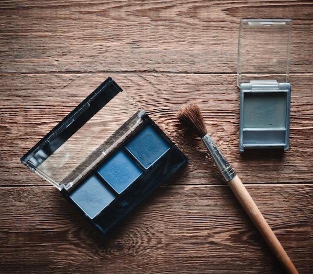 Ombres à maquillage et pinceau sur une table en bois. vue de dessus.