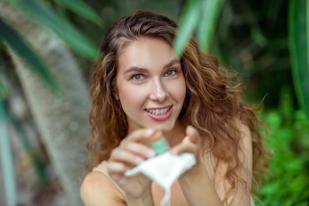 Ombres à paupières. jolie jeune femme souriante tenant un petit pot dans ses mains