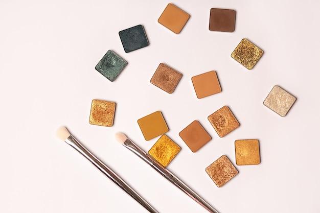 Ombres à paupières simples de couleurs dorées et brunes avec des pinceaux de maquillage sur fond blanc