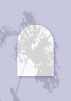 Ombres végétales superposées sur une feuille en forme d'arche de papier blanc texturé sur fond de table violet