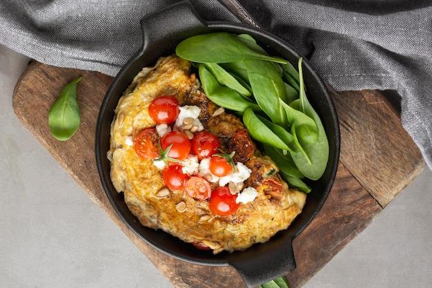 Omelette au fromage et tomates sur une planche à découper