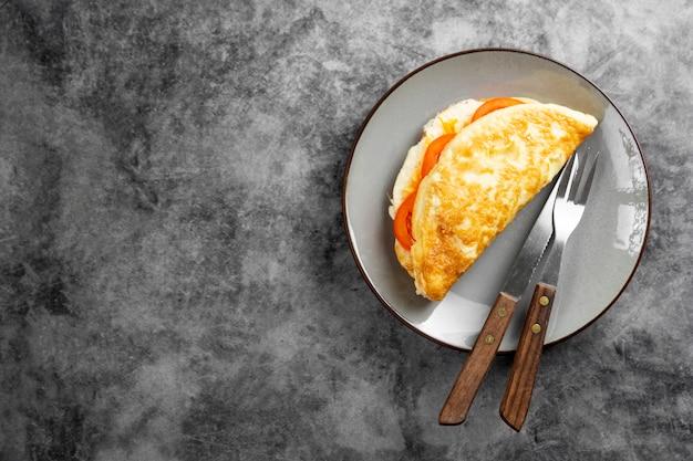 Omelette au fromage et tomates pour le petit déjeuner. vue de dessus avec espace copie.