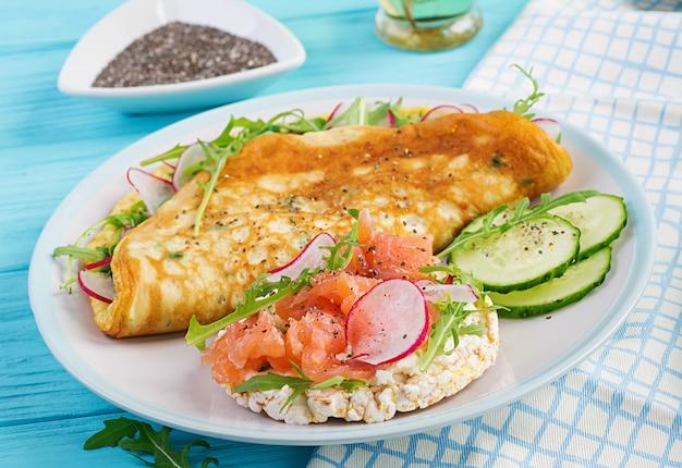 Omelette au radis, roquette verte et sandwich au saumon sur plaque blanche