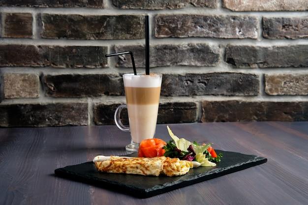 Omelette au saumon sur une assiette en ardoise et une tasse de café au lait