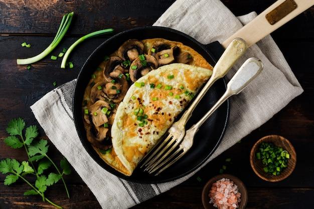 Omelette aux champignons et jeunes oignons verts sur une poêle en fonte sur une vieille surface en bois.