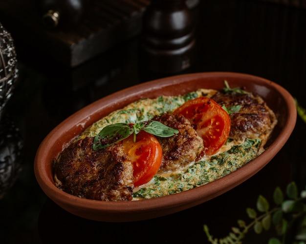 Omelette aux légumes avec cotlets, tranches de tomate et feuilles vertes basilic fraîches