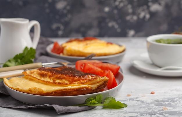 Omelette aux œufs brillante avec fromage et légumes, tasse de thé vert. concept de nourriture de petit déjeuner, espace de copie.