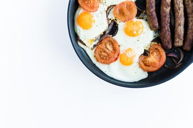Omelette aux tomates dans une casserole sur un fond blanc.