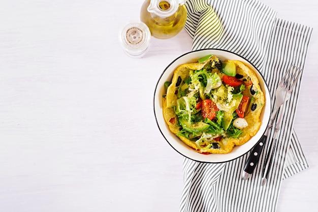 Omelette aux tomates fraîches, aux olives noires, à l'avocat et au fromage mozzarella.