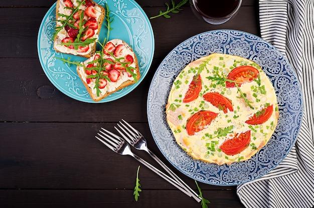 Omelette aux tomates, jambon, oignons verts et sandwich aux fraises sur tableau noir, vue de dessus