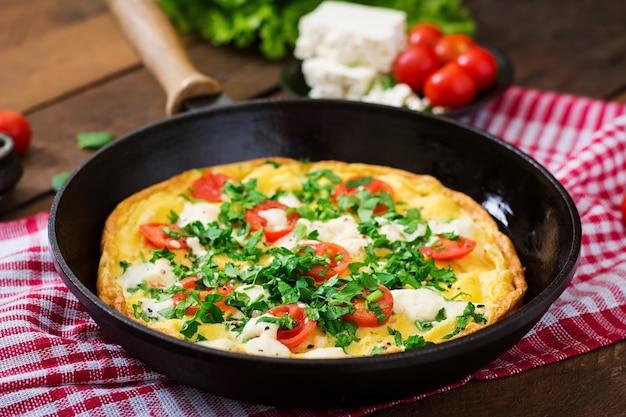 Omelette aux tomates, persil et feta dans une poêle