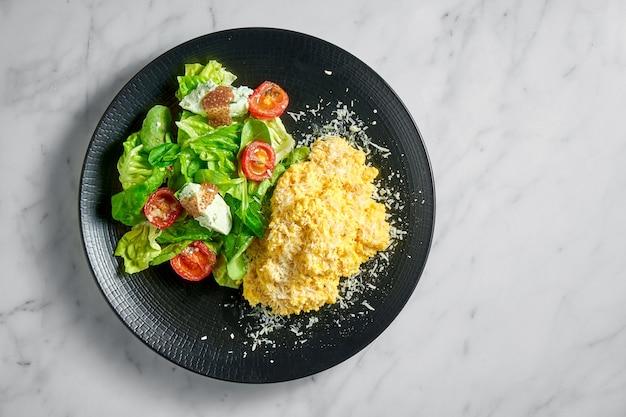 Omelette brouillée avec salade d'épinards, ricotta et tomates cerises, servie dans une assiette noire sur marbre