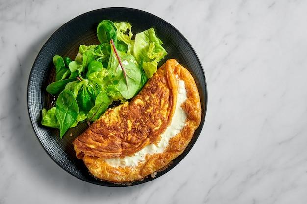 Omelette crémeuse luxuriante farcie avec mélange de salade en plaque noire sur marbre blanc