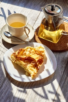 Une omelette dans une assiette sur une table en bois une théière et une tasse