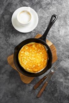 Omelette dans une poêle et une tasse de café. omelette saine fraîchement préparée.