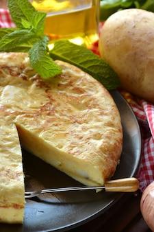 Omelette espagnole aux pommes de terre et aux œufs, accompagnée d'huile d'olive