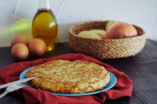 Omelette espagnole aux pommes de terre, œufs et oignons, accompagnée d'huile d'olive