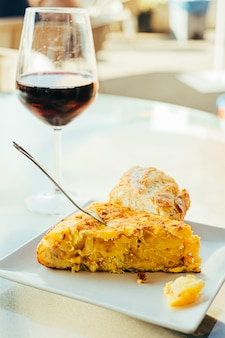Omelette espagnole avec pommes de terre et oignons, et un verre de vin rouge, cuisine espagnole typique.
