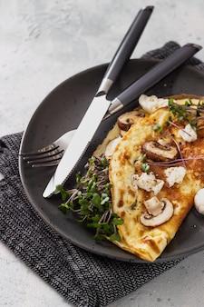 Omelette farcie aux champignons, fromage mozzarella et micropousses pour le petit déjeuner. cuisine à la maison.