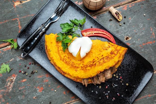 Omelette farcie à la viande, légumes verts, œuf poché. omelette gourmande aux œufs