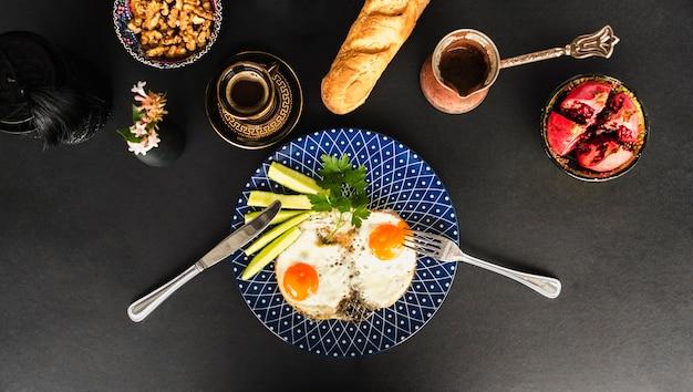 Omelette frite avec thé, pain et bol en noyer sur fond noir