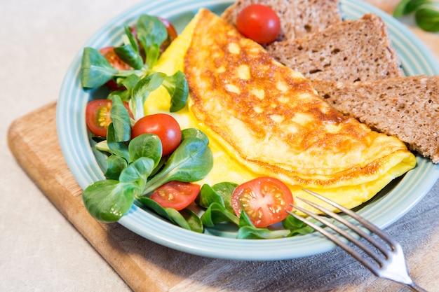 Omelette maison avec salade sur assiette. concept de nourriture saine