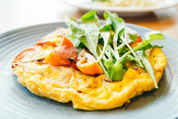 Omelette d'oeufs frits en assiette blanche