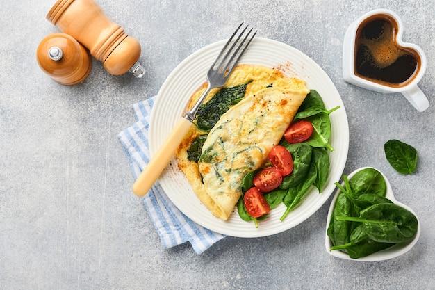 Omelette ou omelette aux épinards, tomate cerise et assaisonnement au poivre sur une assiette blanche, sur fond gris clair. concept de petit-déjeuner sain. vue de dessus.