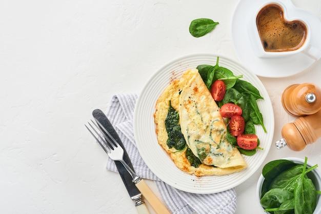 Omelette ou omelette aux épinards, tomate cerise et assaisonnement au poivre sur une plaque blanche, sur fond blanc. vue de dessus.